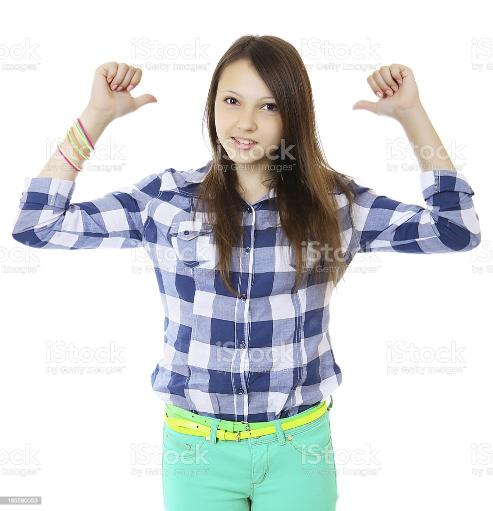 Young teen girl pointing behind with her thumb. stock photo
