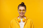 istock Young teen girl wearing t-shirt, hoodie, round colored glasses and wireless headphones around neck, laughing happily, isolated on yellow background 1256944016