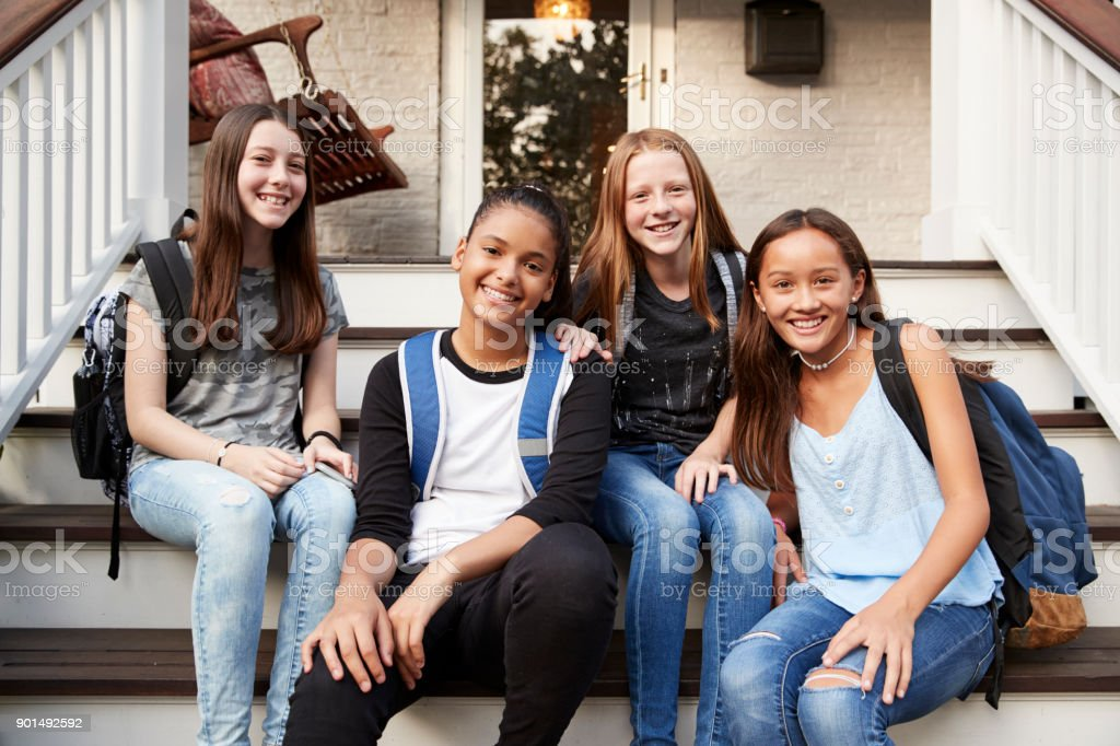 Young teen girls on front steps of house looking at camera stock photo