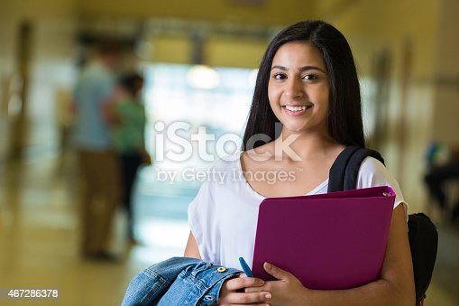 istock Young teen Indian female student in large high school hallway 467286378