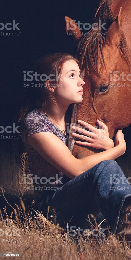 Young teen woman loving her horse with embracing hug stock photo