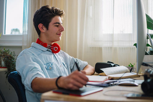 Young teenager from home doing their work or exercise for the exam, deals with graphic design and works in the program Photoshop.