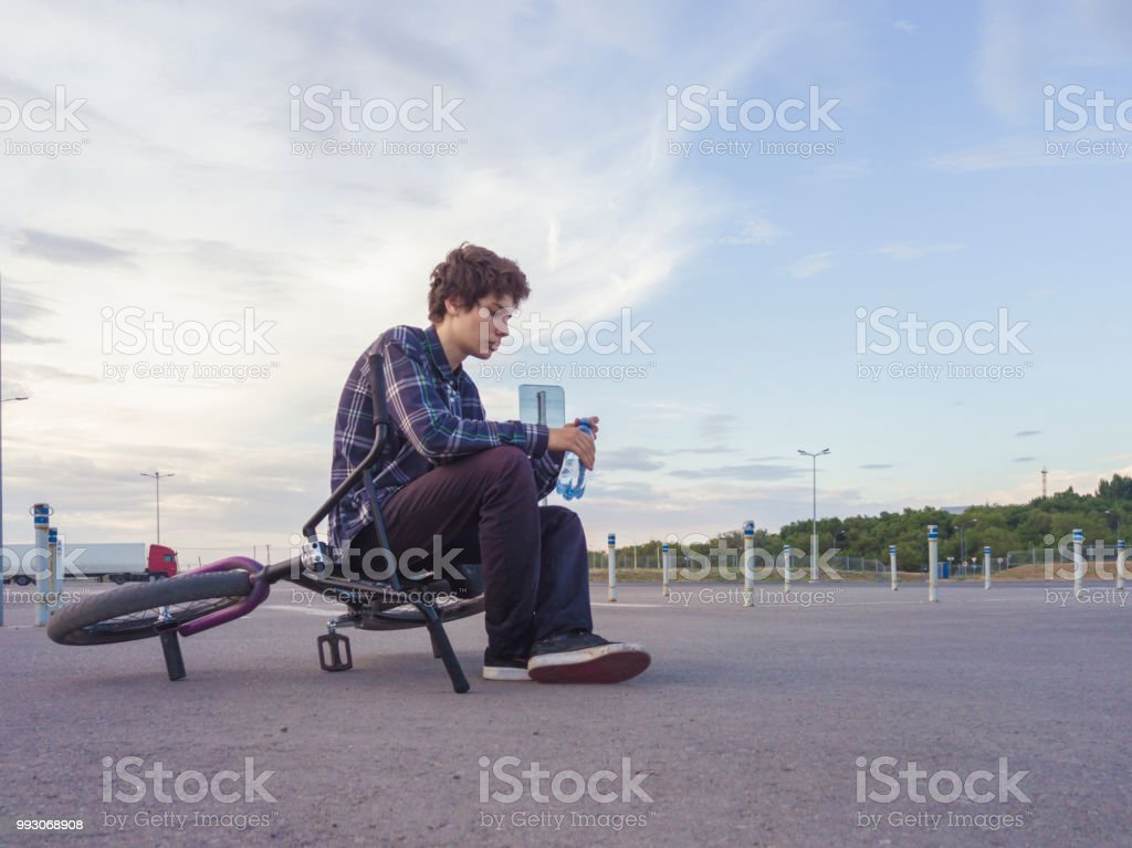 young teenage boy having a rest on the bmx bike on the ground stock photo