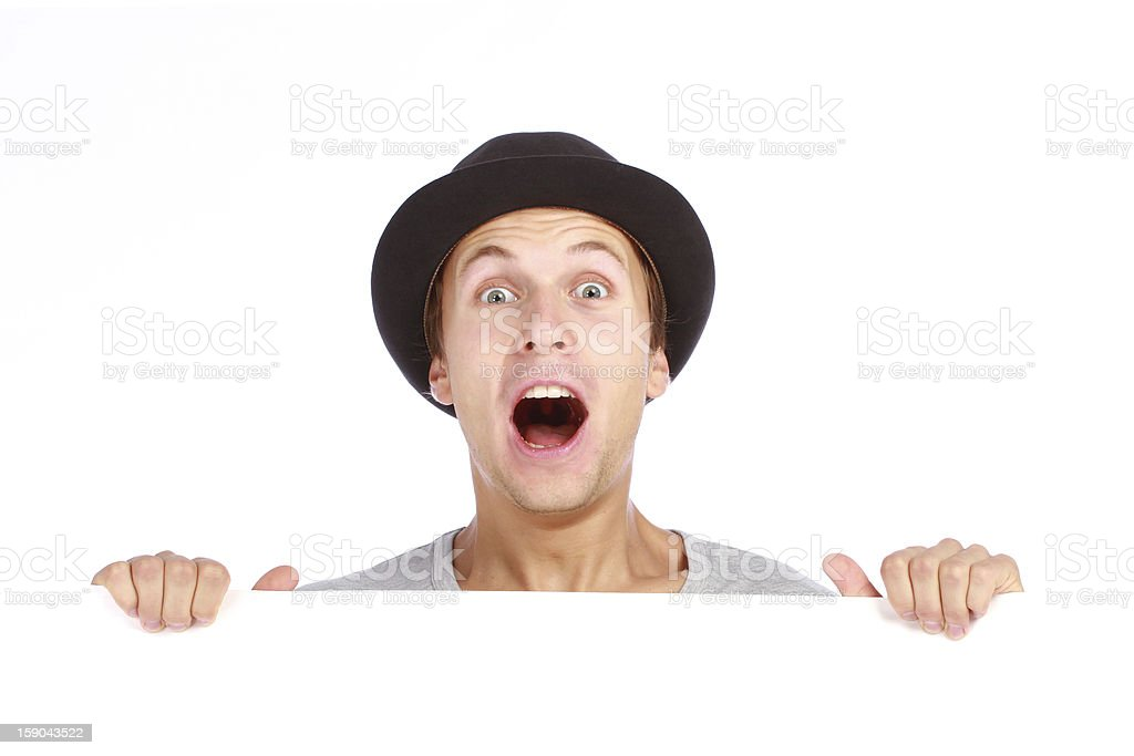 Young teenage boy hiding behind billboard and making face royalty-free stock photo