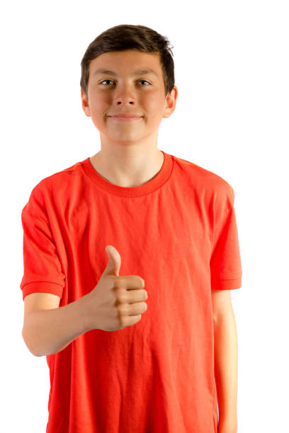Young teenage boy isolated on white giving thumbs up stock photo