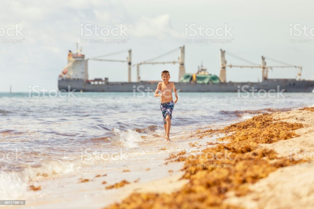 Young teenage boy runs along the beach in Florida stock photo