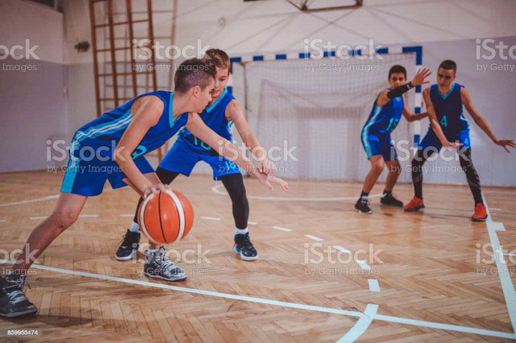 Young teenage boys playing basketball stock photo