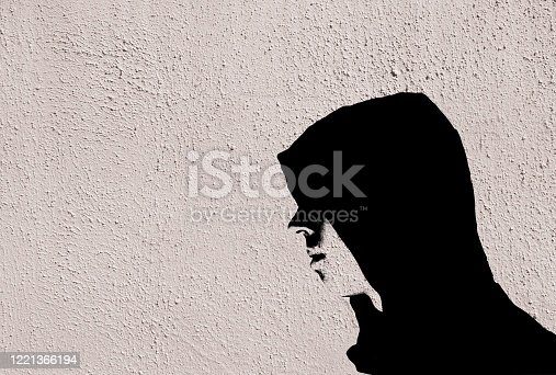 506166130 istock photo Young teenage bully boy in black hoodie with stencil effect on white wall with copy space 1221366194
