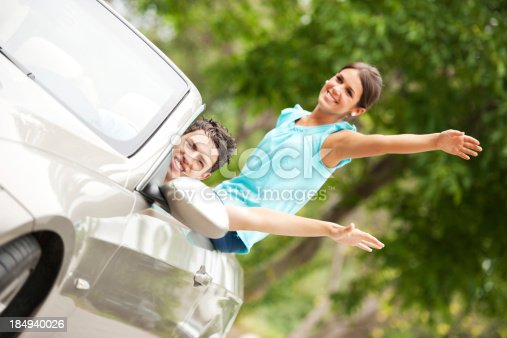 481388538 istock photo Young teenage couple driving in a Convertible car 184940026