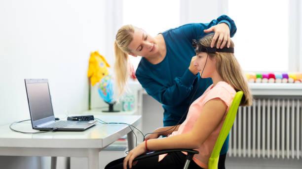 Junge Teenager Mädchen und Kind Therapeuten während EEG Neurofeedback-Sitzung. Elektroenzephalographie-Konzept. – Foto