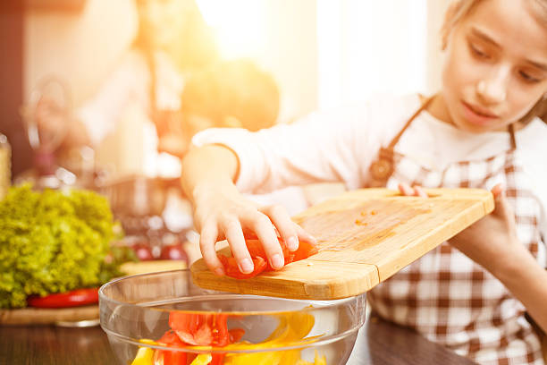 Young teenage girl cook together with her family Young teenage girl cooking together with her family in the kitchen. Cute girl chopping tomatoes for salad sergionicr stock pictures, royalty-free photos & images