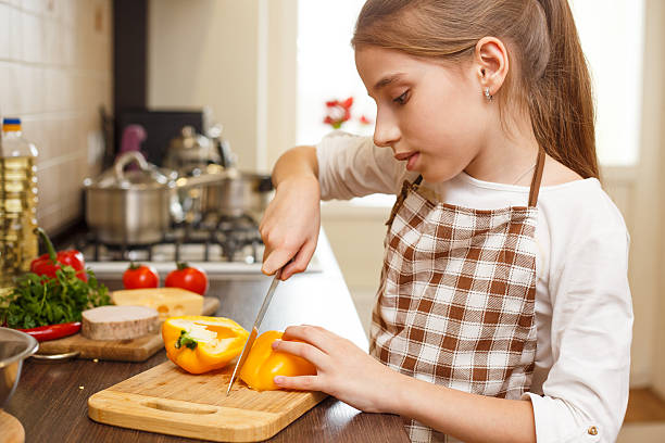 Young teenage girl cutting sweet pepper on board Young teenage girl in apron cutting sweet pepper on board at the kitchen. sergionicr stock pictures, royalty-free photos & images