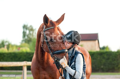 istock Young teenage girl equestrian kissing her chestnut horse. 488313334