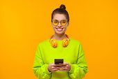 istock Young teenage girl in neon green sweatshirt and glasses, holding smartphone in hands, using app or going to text friends, isolated on yellow background 1247694586