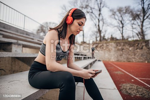 One young teenage girl in sports clothing sitting on the stairs and listening music on the smart phone