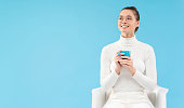 istock Young teenage girl in white turtleneck and glasses, holding cup with coffee or tea, sitting in armchair, looking aside with smile, isolated on blue background with copy space 1252905111