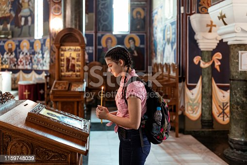 Beautiful Young Female Teenager is Standing by the Altar Inside the Church, Holding a Candle and Praying for Some Hope. Schoolgirl with Long Hair and Backpack is Talking to the God While Holding a Burnt Candle in the Hands. Faith, Spirituality and Religion Concept.