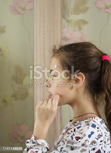 514727472istockphoto Young teenage girl make up acne pimple on her face before a mirror, concept problem on skin 1141148939