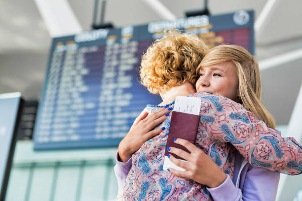 Young teenage girl reuniting with her mother in airport stock photo