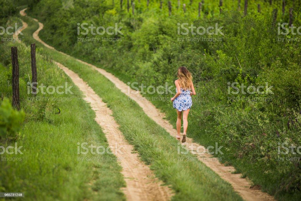 Young teenage girl running on a dirt road. zbiór zdjęć royalty-free