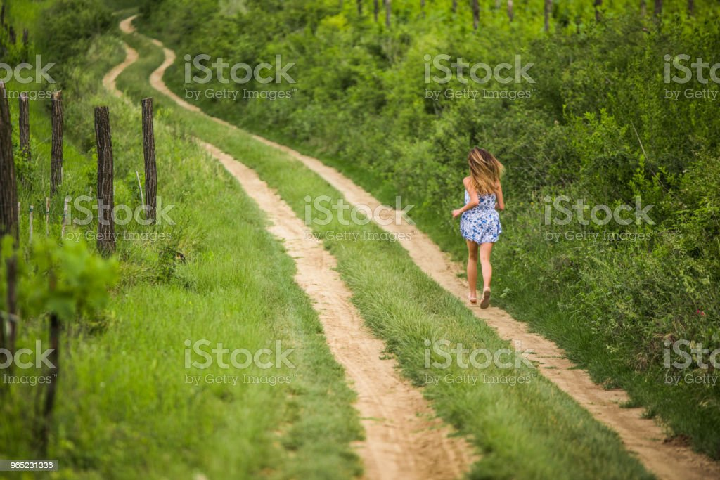 Young teenage girl running on a dirt road. royalty-free stock photo