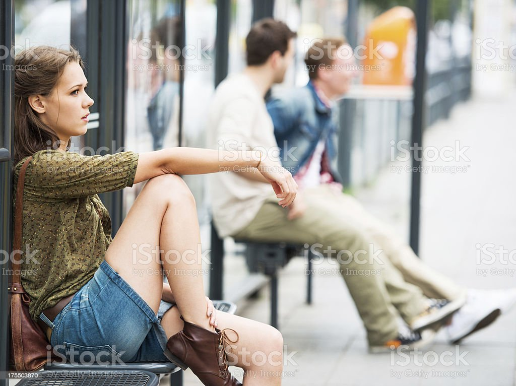 Young teenage girl waiting at the bus stop. stock photo