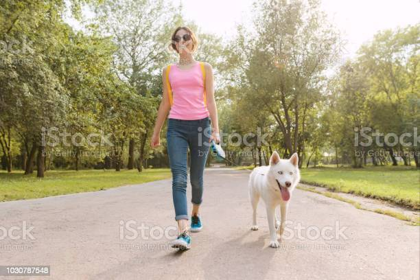 Young teenage girl walking with a dog in the park picture id1030787548?b=1&k=6&m=1030787548&s=612x612&h=im9fggykxnyvoh1dkig55hgwzauer9sbevjqarfjuh8=