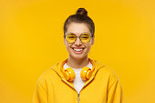 istock Young teenage girl wearing t-shirt, hoodie, round colored eyeglasses and wireless headphones around neck, laughing happily, isolated on yellow background 1227242521
