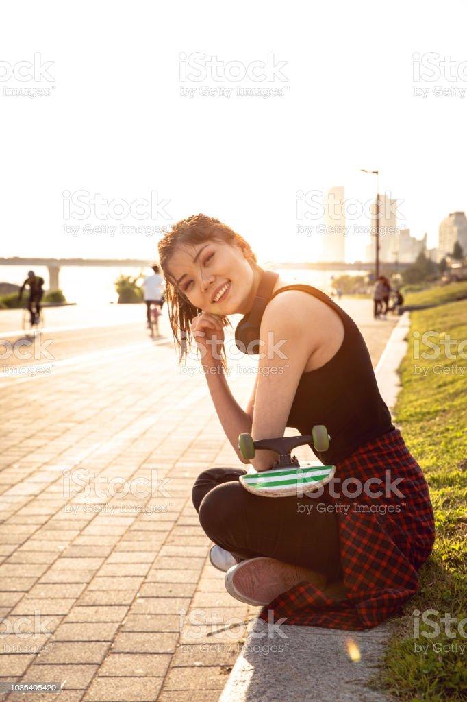 Young teenage girl with skateboard having fun in the city - Seoul South Korea stock photo