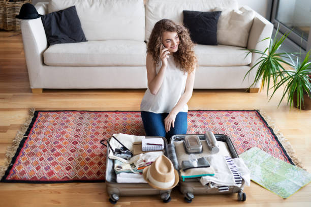 A young teenage girl with smartphone and a map packing for a holiday at home. stock photo