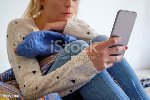 istock Young teenage girll with phone on her bed 862278706