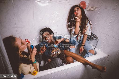 Young multi-ethnic hipster girls having slumber party at home and blowing bubbles in bathtub