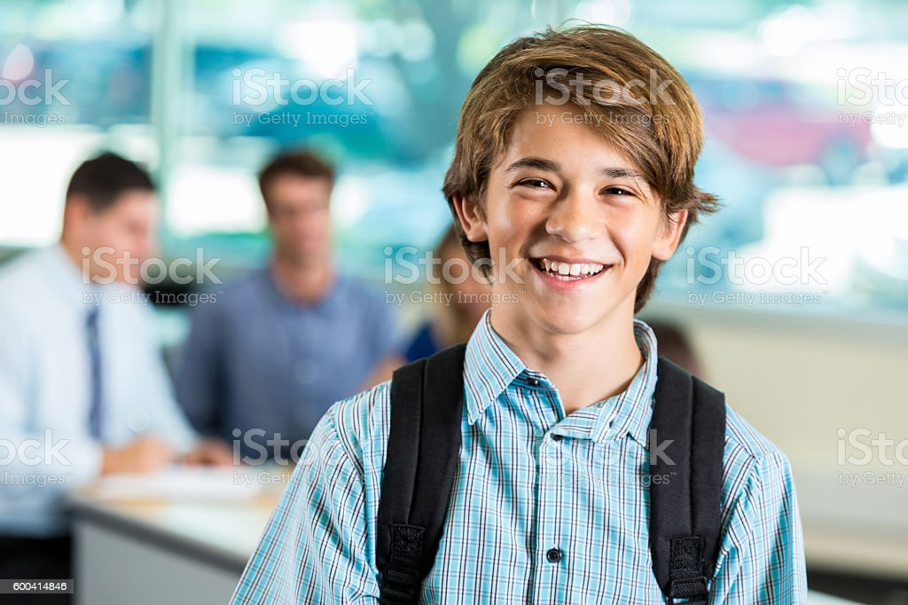 Young teenage male student smiling during parent teacher conference