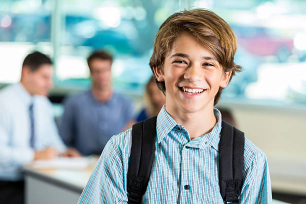 Young teenage male student smiling during parent teacher conference stock photo