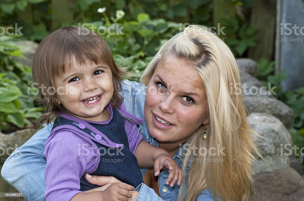Young teenage mother with her child sitting outside royalty-free stock photo