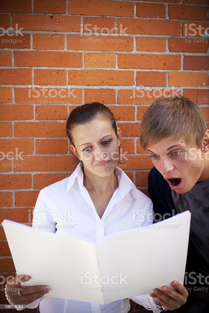 Young Teenager Couple reading a Book with Astonishment royalty-free stock photo