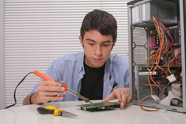 Young teenager fixing a computer stock photo