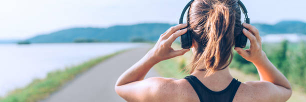Young teenager girl adjusting  wireless headphones before starting jogging and listening to music. Web page header cropping. Young teenager girl adjusting  wireless headphones before starting jogging and listening to music. Web page header cropping. wireless headphones stock pictures, royalty-free photos & images