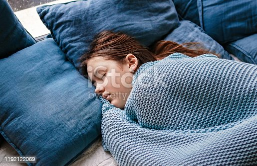 Young teenager girl sleeping snuggled in warm knitted blue blanket. Seasonal melancholy, apathy and winter blues. Cozy home.