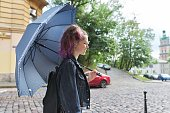 Young teenager girl under an umbrella on the street of old city, copy space