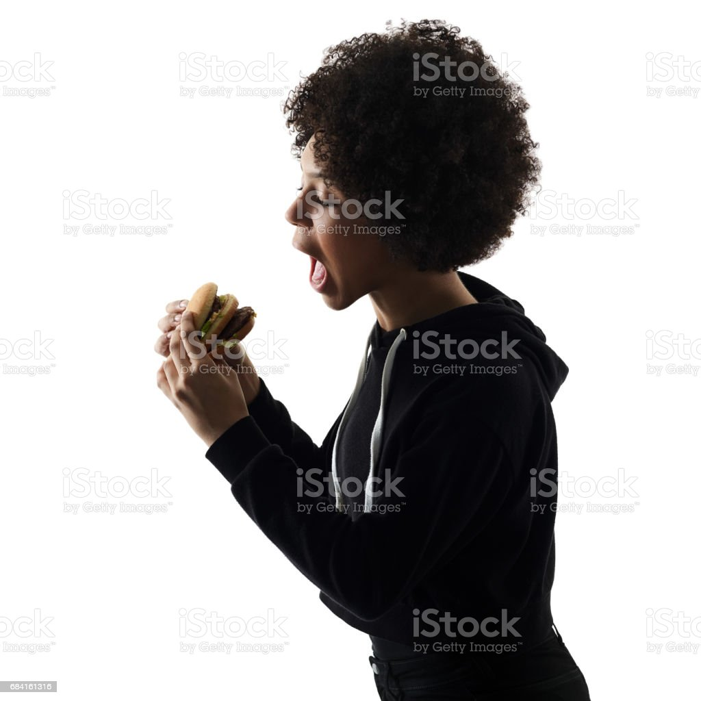 young teenager girl woman eating hamburger shadow silhouette iso royalty-free stock photo