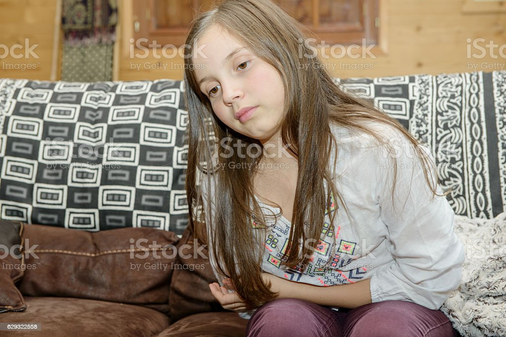 young teenager having a stomachache sitting on sofa stock photo