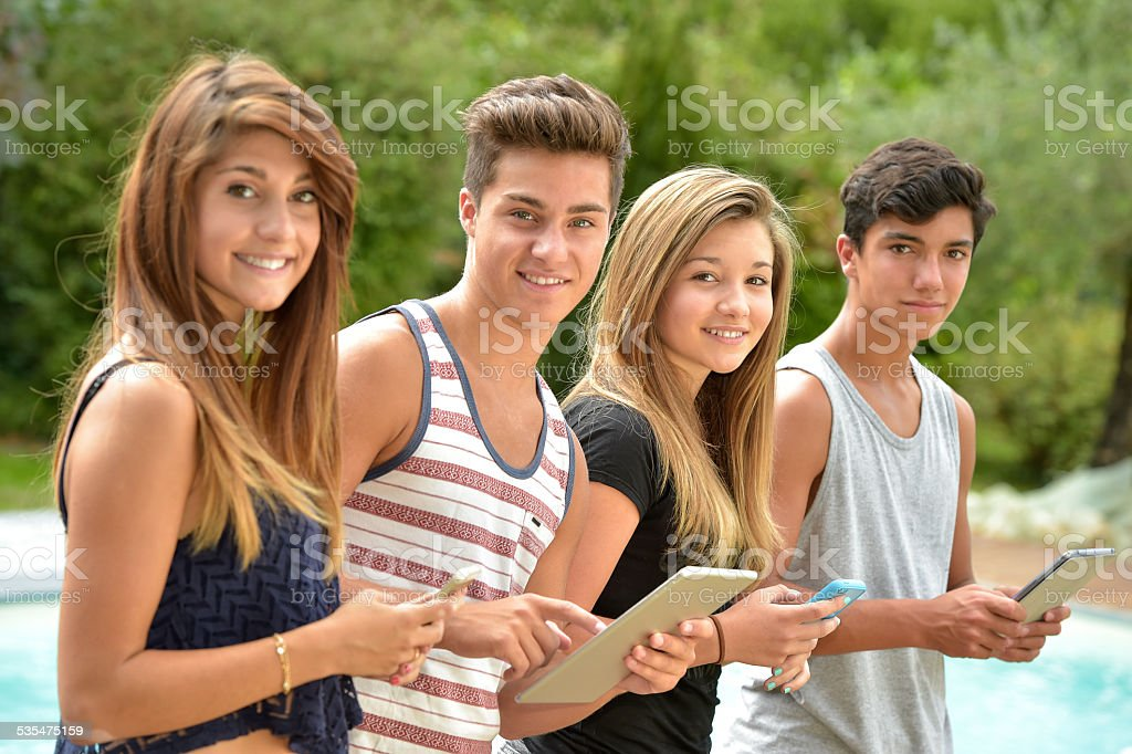 Young teenagers playing on tablet and phone stock photo
