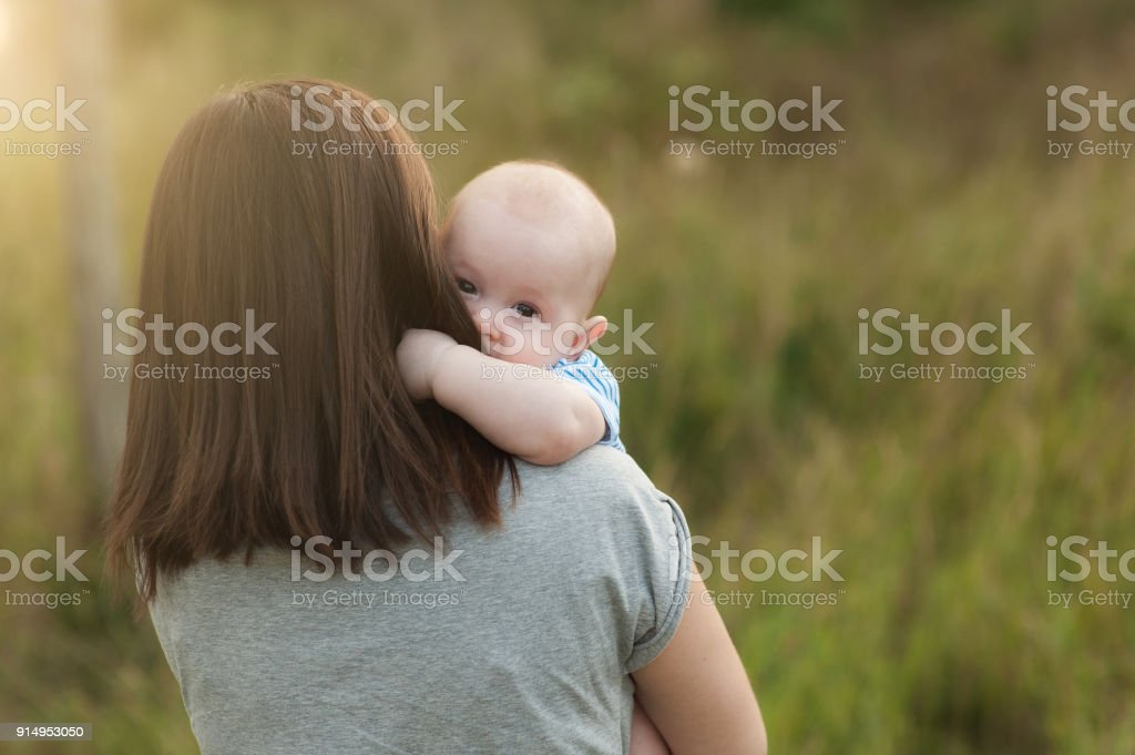 Young tender brunette woman standing at green grass background hugging little cute child baby boy on nature. Mother, little kid son. Parenthood, family day 15 of may, love, parents, children concept. stock photo