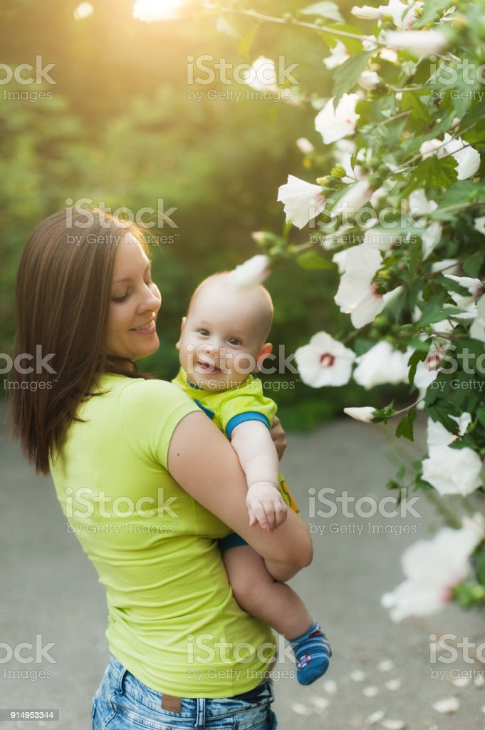 Young tender woman standing near green bush, white flowers background, hugging little cute child baby boy. Mother, little kid son. Parenthood, family day 15 of may, love, parents, children concept. stock photo