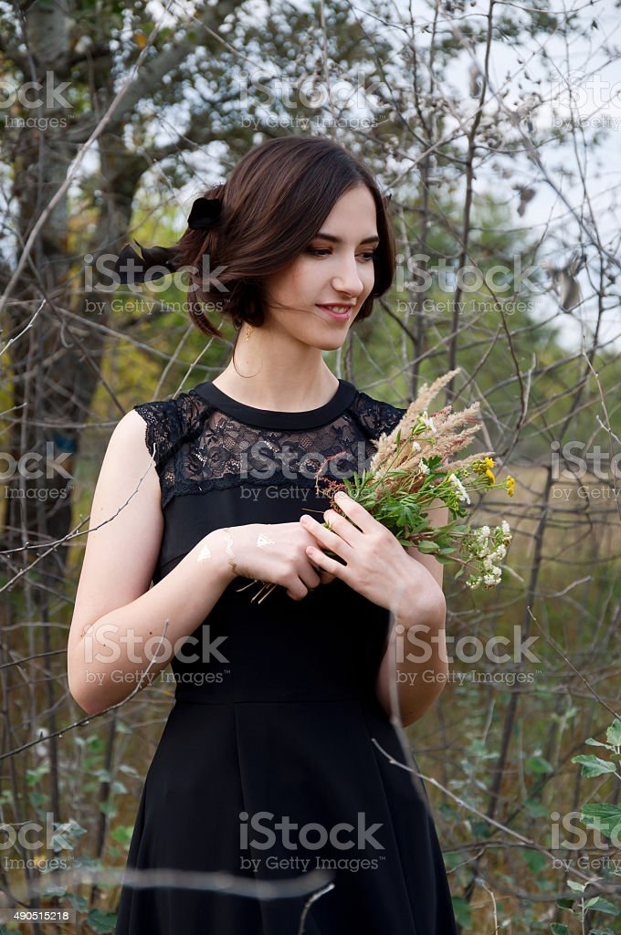 Young tender woman with black hair, field flowers stock photo