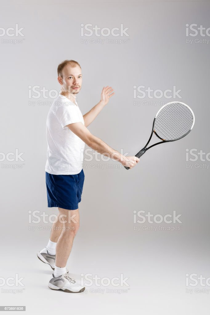jeune tennisman joue au tennis sur fond gris photo libre de droits