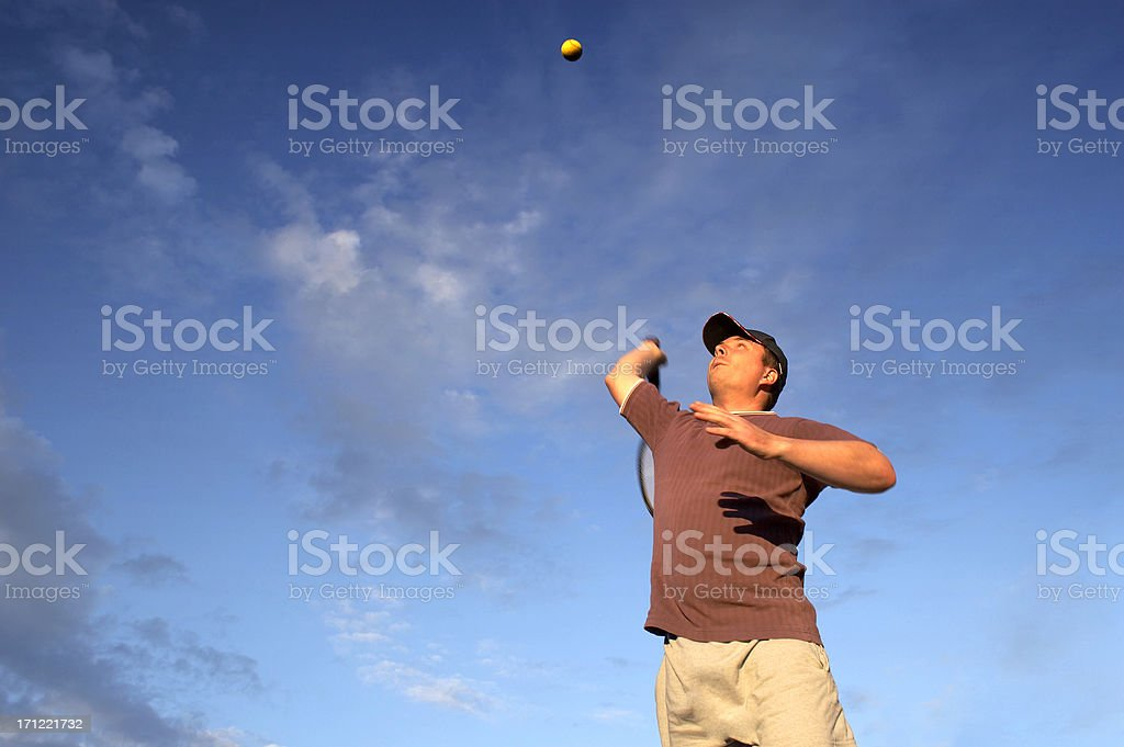 Young tennis player serving royalty-free stock photo