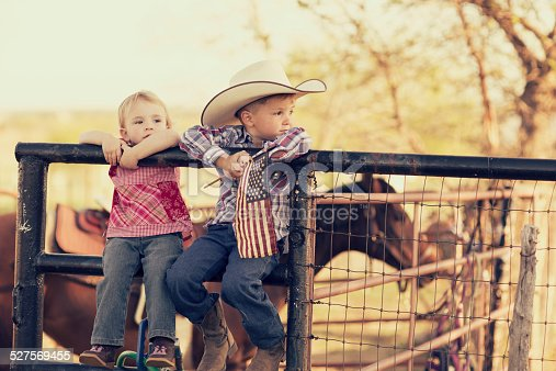 Two young children and siblings pose with the American flag on their farm in Texas. Cowboys and cowgirls.