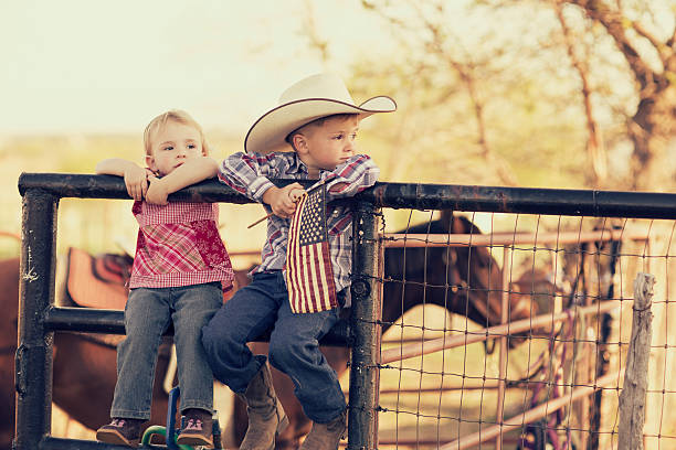 Young Texas Children Two young children and siblings pose with the American flag on their farm in Texas. Cowboys and cowgirls. independence day photos stock pictures, royalty-free photos & images